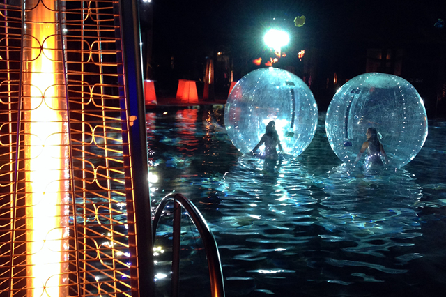 Scantily clad women in huge hamster balls floating on the blue-lit pool?
